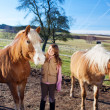Happy young girl between two horses — Stock Photo