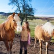 Stock Photo: Happy young girl between two horses