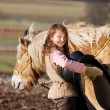Close-up of a young girl carrying saddle — Stock Photo