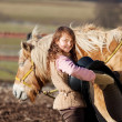 Stock Photo: Close-up of young girl carrying saddle