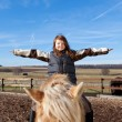 Stock Photo: Happy girl playing on top of her horse