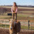 Girl performs acrobatics on top of horse — Stock Photo #26299003