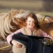 Portrait of a young girl carrying a saddle — Stock Photo