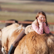 Stock Photo: Playful young happy girl laying in her horse