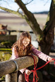 Girl tying reins to a wooden fence — Stock Photo