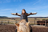 Happy girl playing on top of her horse — Stock Photo