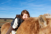 Playful young girl amused while riding her horse — Stock Photo