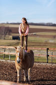 Girl performs acrobatics on top of a horse — Stock Photo