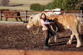 Young girl carrying saddle — Stock Photo