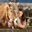 Happy little girl cuddling her horse — Stock Photo