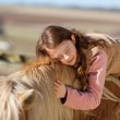 Pretty teenage girl loving her horse — Stock Photo #26300991