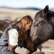 Young girl petting her horse — Stock Photo