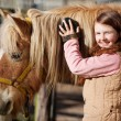 Smiling teenager grooming her horse — Stock Photo #26301027