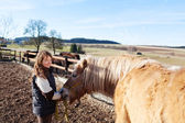Young girl leading her horse — Stock Photo
