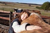 Jong meisje haar paard aaien — Stockfoto