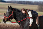 Playful young girl riding on a horse — Stock Photo