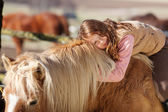 Portrait of a young girl laying on a horse — Stock Photo