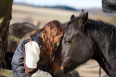 Happy young girl petting her dark bay horse — Stock Photo