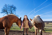 Portrait of a pretty young girl with horses — Stock Photo