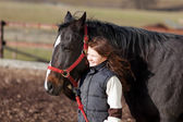 Proud young girl leading her horse — Stock Photo