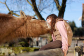 Young girl exchange cuddles with her horse — Stock Photo