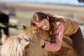 Pretty teenage girl loving her horse — Stock Photo
