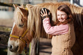 Smiling teenager grooming her horse — Stock Photo