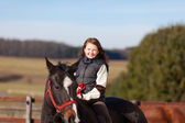 Smiling young girl riding her dark bay horse — Stock Photo