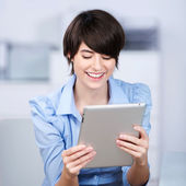 Happy young woman reading a tablet — Stock Photo