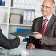 Businessman giving job application to the employer — Stock Photo