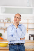 Pensive man in kitchen — Stock Photo