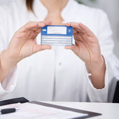 Receptionist Showing Medical Card At Counter — Stock Photo