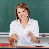 Uśmiechający się nauczyciel sprawdzania jej notatki dla klasy — Zdjęcie stockowe