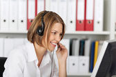 Serious smiling businesswoman talking on headset — Stock Photo