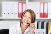 Happy businesswoman talking on headset — Stock Photo
