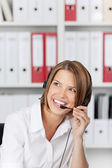 Laughing businesswoman talking on headset — Stock Photo