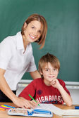 Teacher and elementary school student — Stock Photo