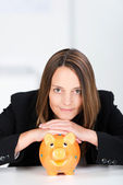 Serious Businesswoman With Piggy Bank At Desk — Stock Photo