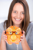 Businesswoman Holding Piggy Bank With Glasses In Office — Stock Photo