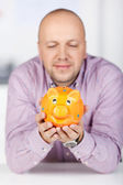 Businessman Holding Piggybank In Office — Stock Photo