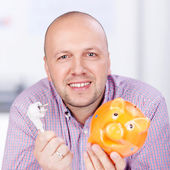 Businessman Holding Piggybank And Electric Plug In Office — Stock Photo