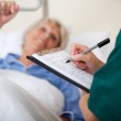 Docotr Writing On Clipboard While Looking At Patient — Stock Photo