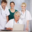 Smiling Doctors With Laptop At Desk In Hospital — Stock Photo