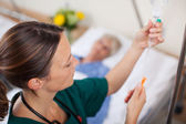 Doctor Adjusting Infusion Bottle With Patient Lying On Bed — Stock Photo