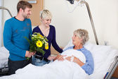 Children With Flowers Visiting Mother In Hospital — Stock Photo
