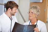 Male And Female Doctors Discussing Xray Report — Stock Photo
