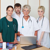 Confident Male And Female Doctors With Laptop At Desk — Stock Photo