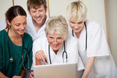 Smiling Doctors Looking At Laptop In Hospital — Stock Photo