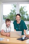 врачи с ноутбуком, опираясь на стол — Стоковое фото