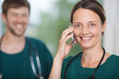 Female Surgeon Using Mobile Phone With Coworker In Background — Stock Photo